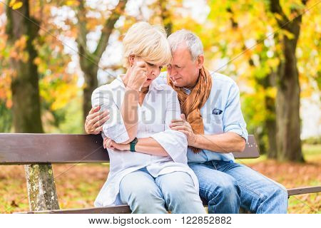 Senior man and woman having being sad embracing each other