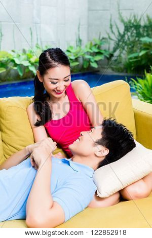 Asian couple huddling on sofa in living room of home or house, a swimming pool in the background