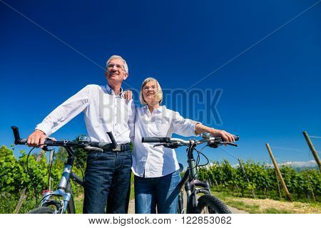 Senior couple enjoying view on bike trip, woman and man leaning against each other