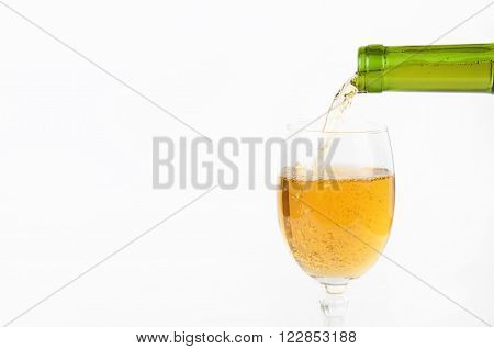 Pouring white wine from bottle into the wineglass closeup on white background with copy space