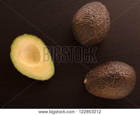 fresh two and half Avocados on a black background