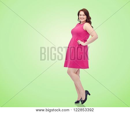 female, portrait and people concept - smiling happy young plus size woman posing in pink dress over green natural background