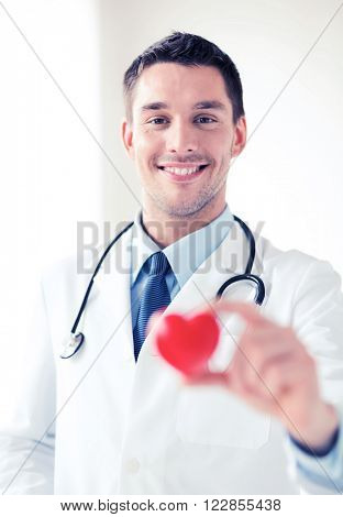 healthcare and medical concept - male doctor with  heart