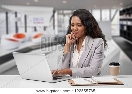 Young Malagasy business lady working on laptop in her office