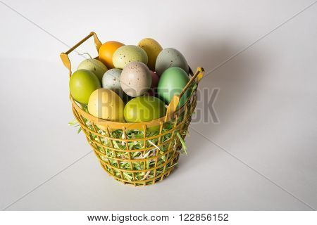 Metal basket filled with a dozen eggs and grass