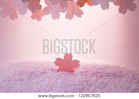 Cherry blossom background image. Shallow depth of field. Cherry blossom pastel pink abstract background. Sakura or cherry flower shaped paper cutouts on soft pink background.