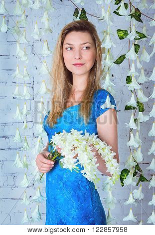 Portrait of beautiful smiling woman in long blue dress  standing near garland made of white artificial bellflowers