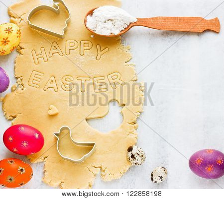 Traditional Easter baking background. Shortcrust pastry for holiday cookies colorful eggs biscuit cutters on white wooden table top view with copy space