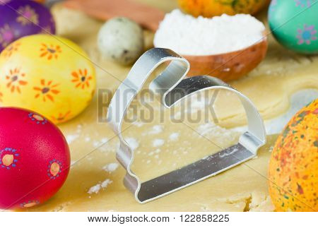 Metal cutter for the Easter cookies in the form of rabbit. Easter food concept: preparation of holiday bunny cookies and colorful eggs. Selective focus