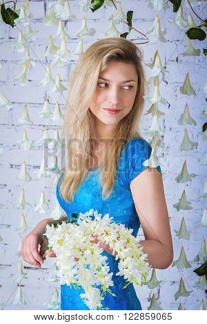 Portrait of beautiful smiling woman in blue dress  standing near garland made of white artificial bellflowers