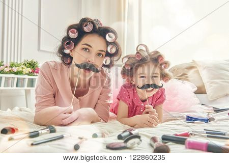Funny family Mother and her child daughter girl with a paper accessories. Mother and daughter preparing for a party and having fun. Beautiful young woman and funny girl with a paper mustache on stick.