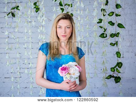 Portrait of beautiful smiling woman in blue dress  standing near garland made of white artificial bellflowers holding peonies bouquet in a small white vase