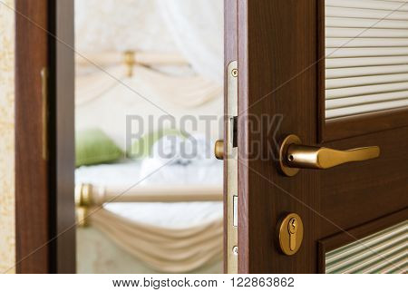 Half opened door of a bedroom. Hotel bedroom door half open. Hotel room welcome guests. Opening door closeup. Door handle. Privacy, intimacy concept. Entrance to the hotel bedroom.