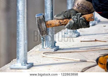 Anchoring metal fence in concrete focus on hammer ** Note: Soft Focus at 100%, best at smaller sizes