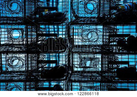 stacked steel lobster traps silhouetted against blue water