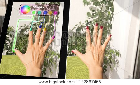 Woman adjusting her fingernail color with a tablet augmented reality concept