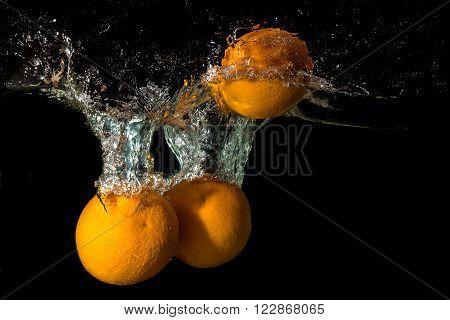Three orange fell into the water lifting splashes on black background