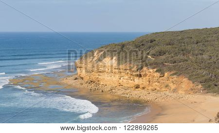 salty sea waves splashing and lapping on the beautiful rocky coast of yellow sand and large rocks and form a white foam and sea skyline in the distance