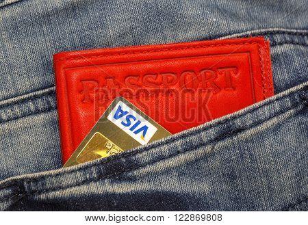 KHARKIV, UKRAINE - MARCH 16, 2016:  Passport, credit cards Visa  sticking out of the pocket of jeans