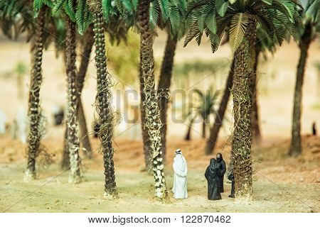 Little figurines of Arabs in the desert oasis under the palm trees. Artistic symbolic objects.