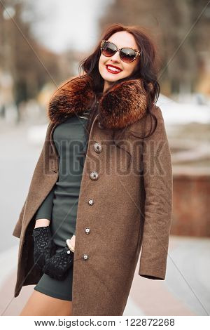 beautiful sexy glamorous brunette girl in an elegant green dress and fur coat with a fluffy fur, gloves and stylish sunglasses outdoors. young woman with chic long dark hair and trendy makeup posing and smiling at the camera