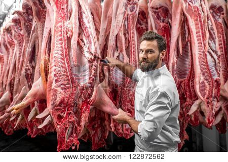 Handsome butcher cutting pork carcasse at the meat manufacturing