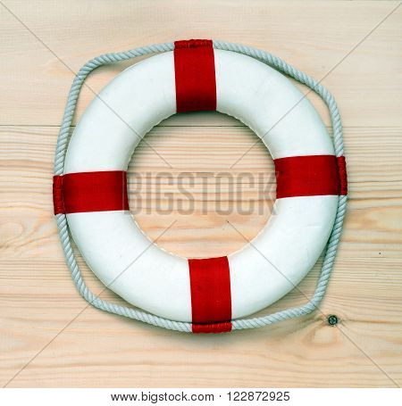 Lifebuoy close up against from wooden boards.
