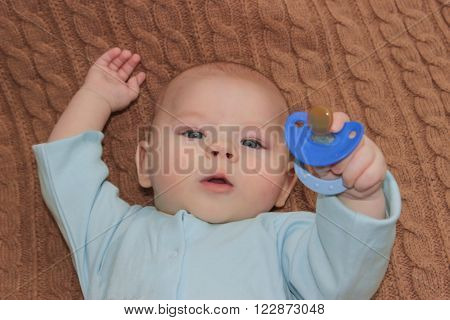 Baby Boy Holding A Blue Nipple