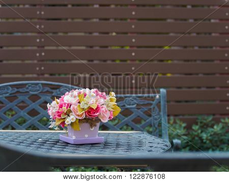 Flowerpot on vintage table and bench in outdoor garden and battens background Copy Space Vintage