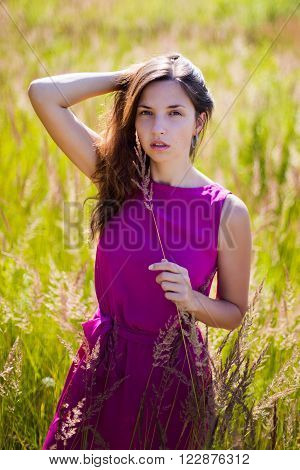 portrait of a young girl with long hair in a field with grass in a purple dress