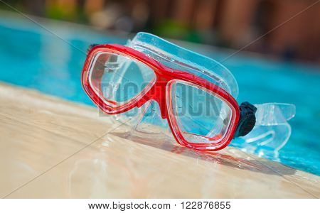 Red mask for diving on blue water background