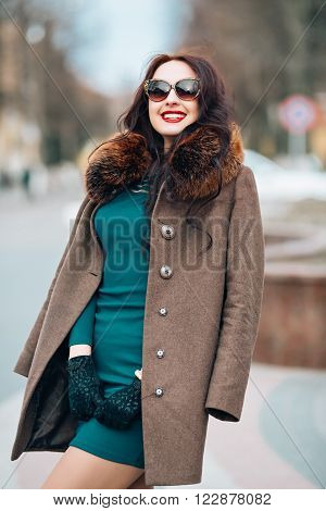 beautiful smiling young woman with long dark hair chic, glamorous sexy brunette girl outdoors, in the street, wearing a green dress and warm coat with fur hood and stylish sunglasses trendy makeup