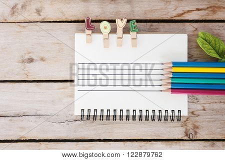 multicolor pencil, vintage book and love text on the wooden, valentine's day for background