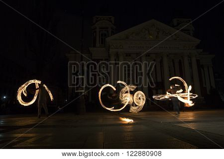 Sofia, Bulgaria - March 19, 2016: Performers are spinning torches while performing a fire show at night celebrating the international Earth hour event in Sofia Bulgaria. Long exposure.