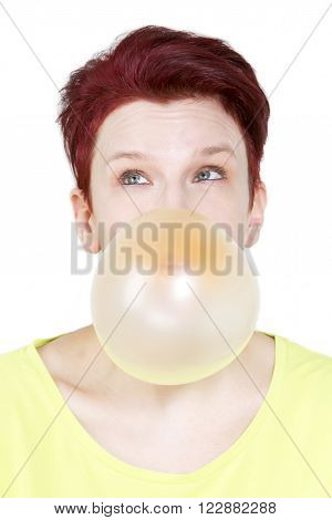 red-haired woman blowing a big bubble of chewing gum