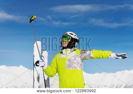 Woman skier stand on top of the mountain in ski helmet and mask taking photo with selfie stick