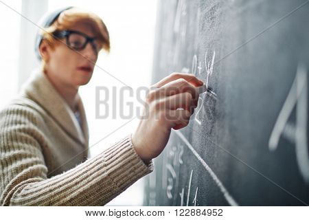 Young college student writing on blackboard during a math class