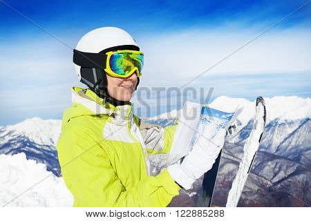 Mountain skier woman stand with map of pistes wearing helmet and ski mask