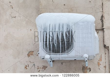 Air conditioner with frozen ice and icicles. Cooling cold temperature concept image. Aged wall background.