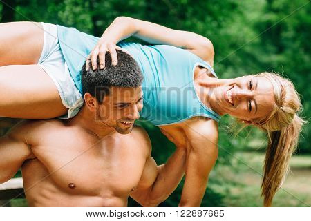 Cheerful fitness couple exercising in nature. Male carrying female on his shoulders