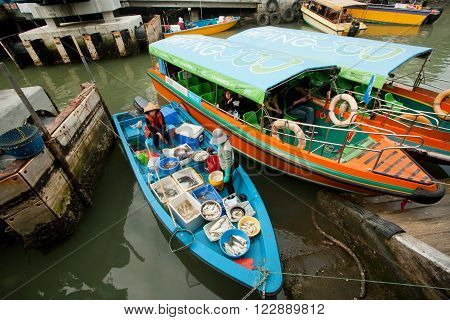 HONG KONG, CHINA - FEB 11: Female traders selling fish and seafood from riverboat of fishing village Tai O on February 11, 2016. Hong Kong dollar is the eighth most traded currency in the world.