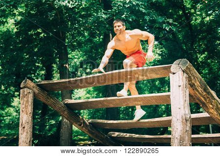 Young muscular build male exercising on fitness trail ** Note: Visible grain at 100%, best at smaller sizes