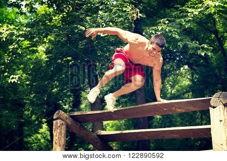 Young muscular build male exercising on fitness trail