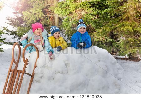 Group of kids in snow fortress throw snowballs