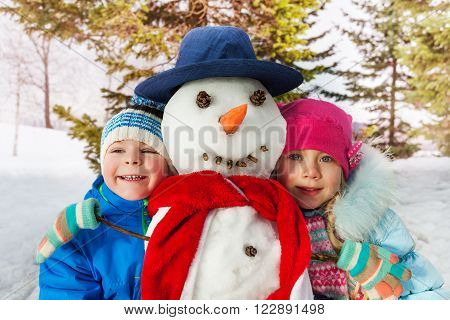 Little boy and girl stand with snowman outside in the forest