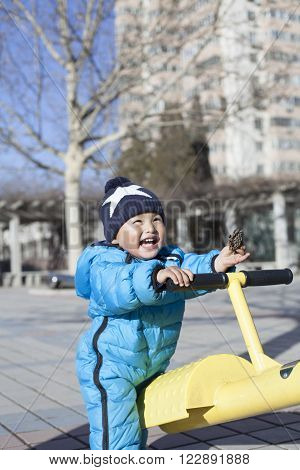 Cute Chinese Baby Boy Playing Seesaw Outdoors