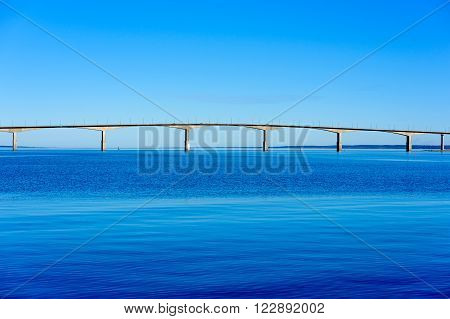 The bridge between Oland and mainland Sweden as seen from Kalmar. The sun is getting low which gives the bridge somewhat of a glow against the blue surrounding water and sky. Cars on bridge.