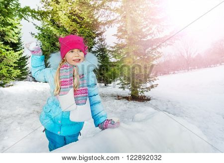 Little girl behind the snow wall throw snowball and smile