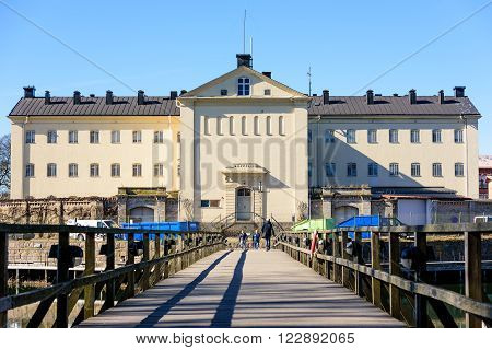Kalmar Sweden - March 17 2016: The prison building as seen from the western city gate across the wooden bridge. People walking over the bridge. Real people in everyday life.