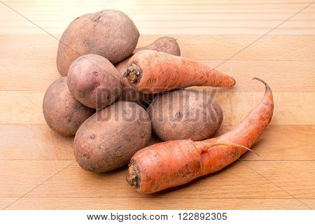 Natural potatoes and carrots on a wooden cutboard
